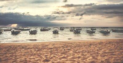 Small boats at a tropical beach at sunset, color toning applied, Sri Lanka.