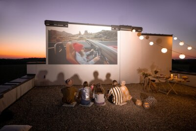 Obraz Small group of people watching movie on the rooftop terrace at sunset. Open air cinema concept. Romantic leisure and entertainment on the roof of a country house