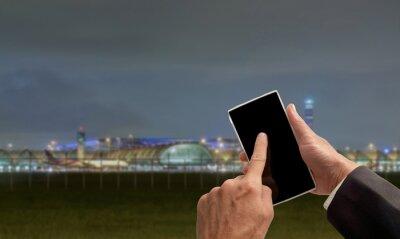 Smartphone / Widok strony przedsiębiorców dociskowych smartphone z rozmycia lotniska na tle nocy.