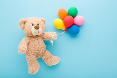Obraz Smiling brown teddy bear holding heap of colorful balloons on light blue table background. Pastel color. Closeup. Congratulation concept. Top down view.