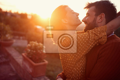 Obraz Smiling couple hugging and kissing at sunset.