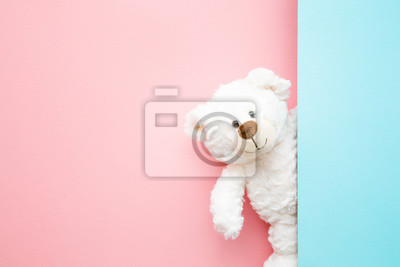 Obraz Smiling white teddy bear looking behind pastel blue wall. Mock up for happy, positive idea. Empty place for inspiration, emotional, sentimental text, quote or sayings on pink background. Front view.