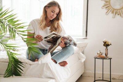 Obraz Smiling young beautiful woman reading magazine