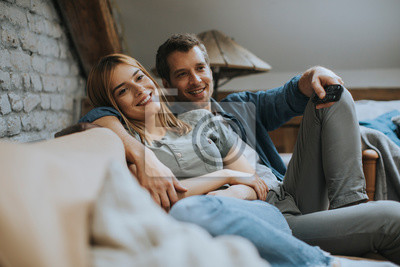 Obraz Smiling young couple relaxing and watching TV at home