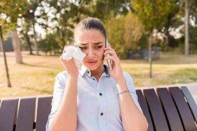 Obraz Smutna młoda kobieta płacze podczas rozmowy na zewnątrz telefonu komórkowego