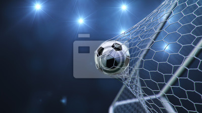 Obraz Soccer ball flew into the goal. Soccer ball bends the net, against the background of flashes of light. Soccer ball in goal net on blue background. A moment of delight. 3D illustration