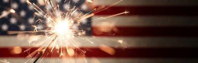 Obraz Sparks flying off a burning sparkler in front of the US American flag for patriotic 4th of July celebration.