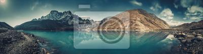 Obraz Spektakularna sceneria krystalicznie czystego jeziora Gokyo na tle potężnego ośnieżonego Himalajów. Siła i piękno dziewiczej przyrody. Idealny obraz do tła i tapet.