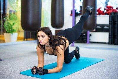 Obraz sportowiec sporty szczupła kobieta robi ćwiczenia jogi w siłowni bilansującego wyciągniętą na jednym kolanie. Fitness, sport, szkolenia