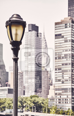 SRetro toned picture of a street lamp with New York City blurred skyline in background, USA.