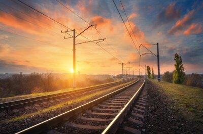 Stacja kolejowa przeciwko piękne niebo o zachodzie słońca. Przemysłowy krajobraz z kolei, kolorowe błękitne niebo z czerwonych chmur, słońce, drzewa i trawa zielona. węzeł kolejowy. Przemysł ciężki. W