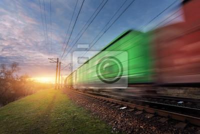 Stacja kolejowa w wagonach towarowych i pociągu w ruchu przeciw słoneczne niebo z chmurami w godzinach wieczornych. Wagony rozmazany. Kolorowe krajobraz przemysłowy. Kolej na zachód słońca. Platforma