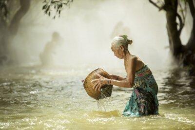 Obraz Stara kobieta szuka strumieni ryb.