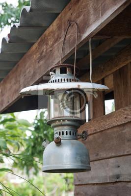 Stara latarnia (lampy) wisi na drewnianej.