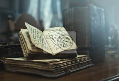 Obraz Stare książki z antykami cyrylica tekstu leżącego na stole w ciemnym pomieszczeniu biblioteki. Edukacja i nauka koncepcji.