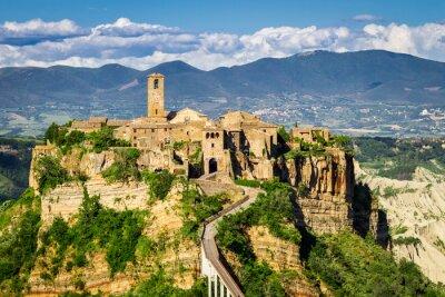Obraz Starożytne miasto na wzgórzu w Toskanii na tle gór.