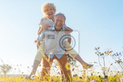 Obraz Starszy mężczyzna niosący żonę na plecach ma zdrowy kręgosłup
