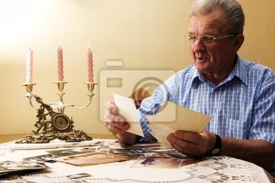 Starszy mężczyzna patrząc na stare fotografie. Opowiadać wspomnienia