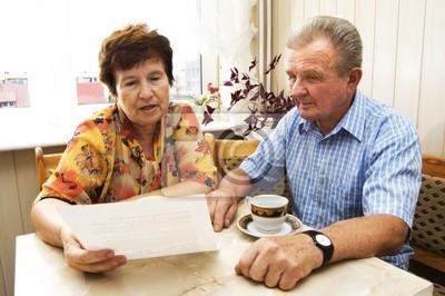 Starszy para studiuje dokumentu razem w domu