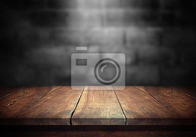 Obraz Stary drewno stół z zamazaną betonową blok ścianą w ciemnego pokoju tle.