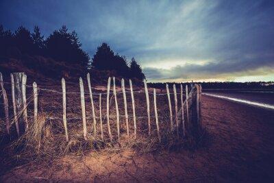 Obraz Stary płot na plaży o zachodzie słońca