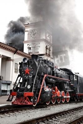 Obraz Stary pociąg parowy opuszcza stację. Archiwalne silnik parowy pociąg lokomotywa porusza się w kierunku kamery tory kolejowe.