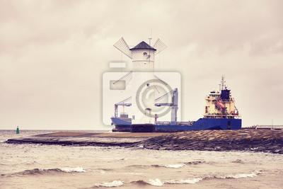 Statek towarowy opuszcza port Świnoujścia w Polsce, kolorowo stonowany obraz.