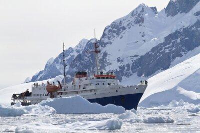 Obraz Statek turystyczny wśród gór lodowych na tle mountai