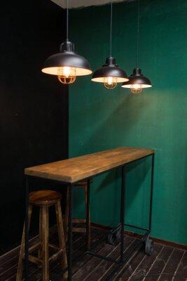 Stelaż na kółkach w kuchni z wiszącymi światłami i drewnianymi stołkami barowymi na tle zielonych i czarnych ścian