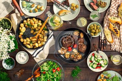 Obraz Stół z grillem, pieczone ziemniaki, różne potrawy