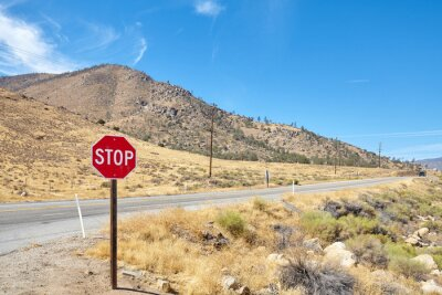 Stop sign by a road in Nevada, focus on traffic sign, USA.