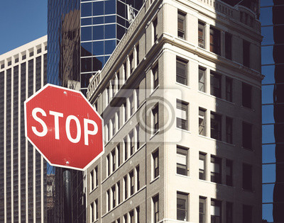 Stop sign on a street of New York City, color toned picture, selective focus, USA.