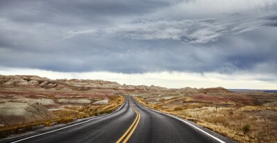 Stormy clouds over road in Badlands National Park, travel concept, South Dakota, USA.