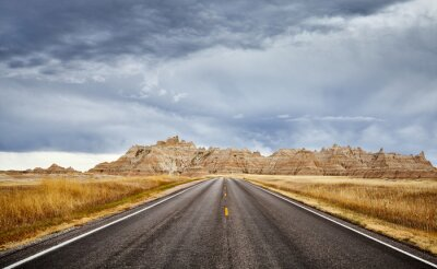 Stormy clouds over road in Badlands National Park, travel concept, USA.