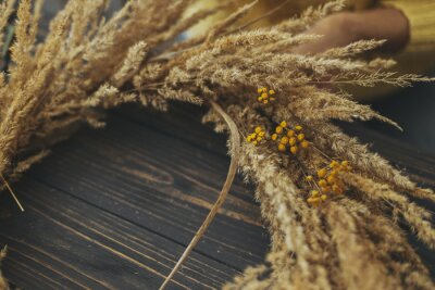 Obraz Stylish autumn boho wreath with dry grass and wildflowers on rustic wooden background. Making rustic autumn wreath with pampas grass and yellow tansy flowers, holiday workshop