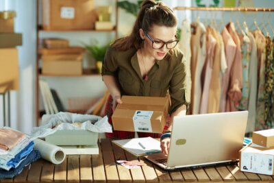 Obraz stylish small business owner woman using laptop in office