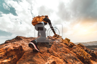 Obraz Success woman hiker hiking on sunrise mountain peak - Young woman with backpack rise to the mountain top. Discovery Travel Destination Concept