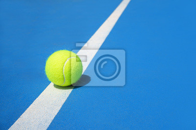 Obraz Summer sport concept with tennis ball on white line on hard tennis court blue color.