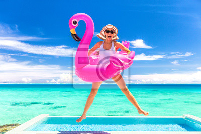 Obraz Summer vacation fun funny woman jumping with flamingo swimming pool float around waist excited of tropical hotel holiday.