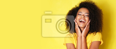 Obraz Super happy afro-american girl isolated on yellow background.