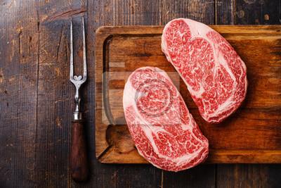 Obraz Surowe świeże mięso marmurowe Steak Ribeye Black Angus i widelec mięsa na drewnianym tle kopia przestrzeń