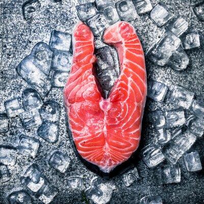 Obraz Surowy pstrąg udziałów i lód na tle metalu.
