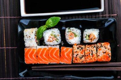 Obraz sushi rolkach asortyment na czarnej tablicy i pałeczki. Tradycyjne rolki na naczynia.