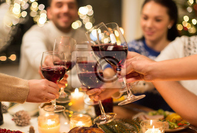 Obraz święta i święto koncepcji - bliska szczęśliwych przyjaciół o świąteczny obiad w domu, picie czerwonego wina i szczęk szklanki