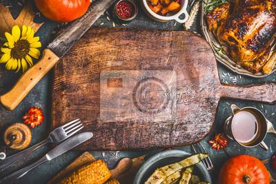 Obraz Święto Dziękczynienia obiad w tle z indykiem, sosem, warzywami z grilla, kukurydzą, sztućcami, dyni, opadaniami liśćmi i kwiatami wokół drewnianej łopatki, widok z góry.