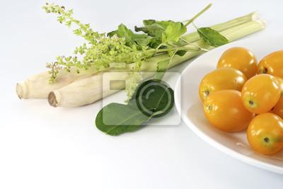Świeże warzywa / żółty pomidor, kaffir liście limonki, bazylia, trawa cytrynowa na białym stole z miejsca kopiowania.
