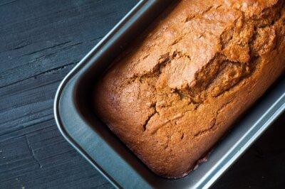 Obraz Świeżo upieczony chleb z dyni ciasto na blasze do pieczenia. Idealny w jesień i podawane na czarnym drewnianym stole.