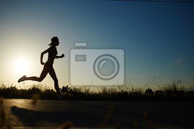 Obraz Sylwetka atletyczna dziewczyna uruchomiony w dół drogi do zachodu słońca