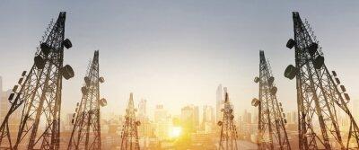 Obraz Sylwetka, wieże telekomunikacyjne z anten telewizyjnych i anteny satelitarnej na zachód słońca, z podwójnym miasta ekspozycji w tle wschód słońca
