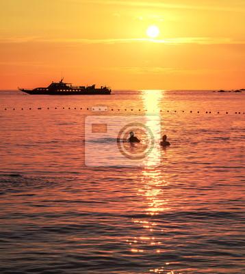 Sylwetki i para pływanie statkiem o zachodzie słońca.